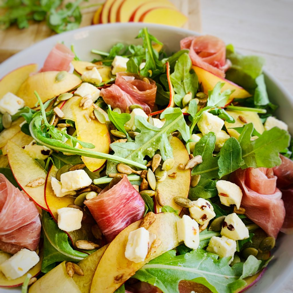 Nectarine, arugula, prosciutto salad topped with feta cheese and pumpkin seeds.